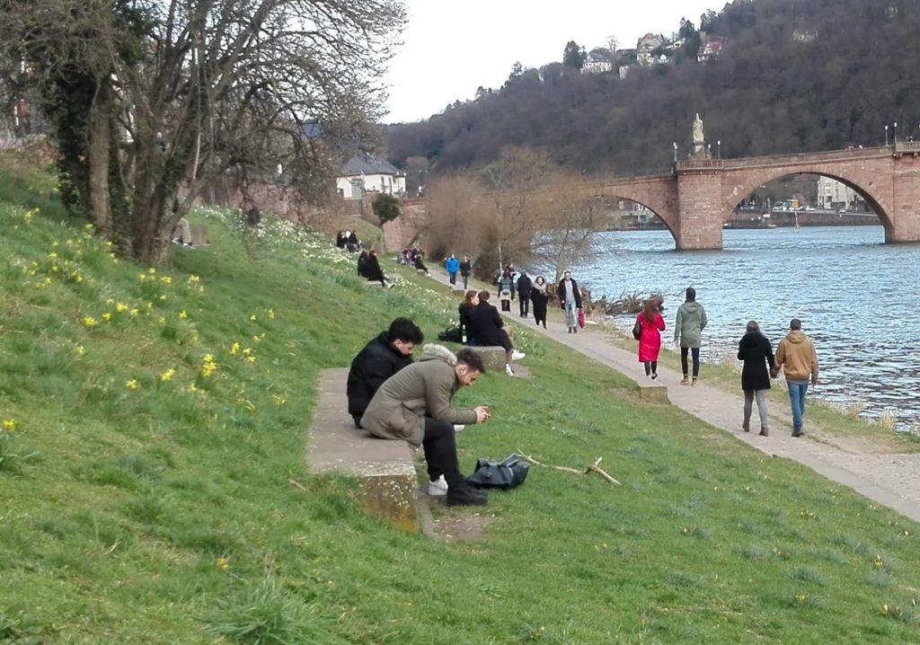 Foto vom nördlichen Neckarufer mit Blick auf die alte Brücke. Viele Leute sitzen auf den Steinbänken im Rasen und genießen die Frühlingssonne.